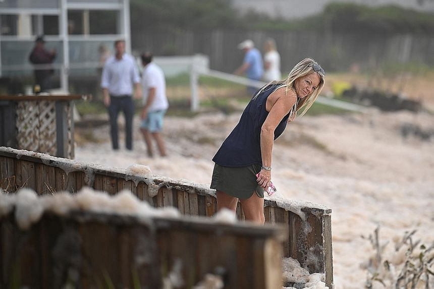 Residents of Sydney's Collaroy suburb inspecting their homes for damage after storms uprooted trees and resulted in houses being coated in ocean foam.