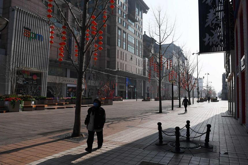 A woman walks in the normally bustling Wangfujing shopping street in Beijing, where the coronavirus outbreak has taken a toll on small-to-medium sized businesses, on Feb 10, 2020.
