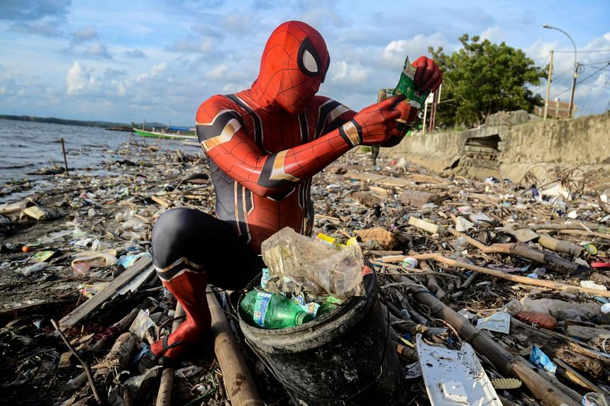Rudi Hartono, a man dressed in Spider-Man costume, looks at plastic waste as he collects rubbish at a beach in Parepare, South Sulawesi province, Indonesia.