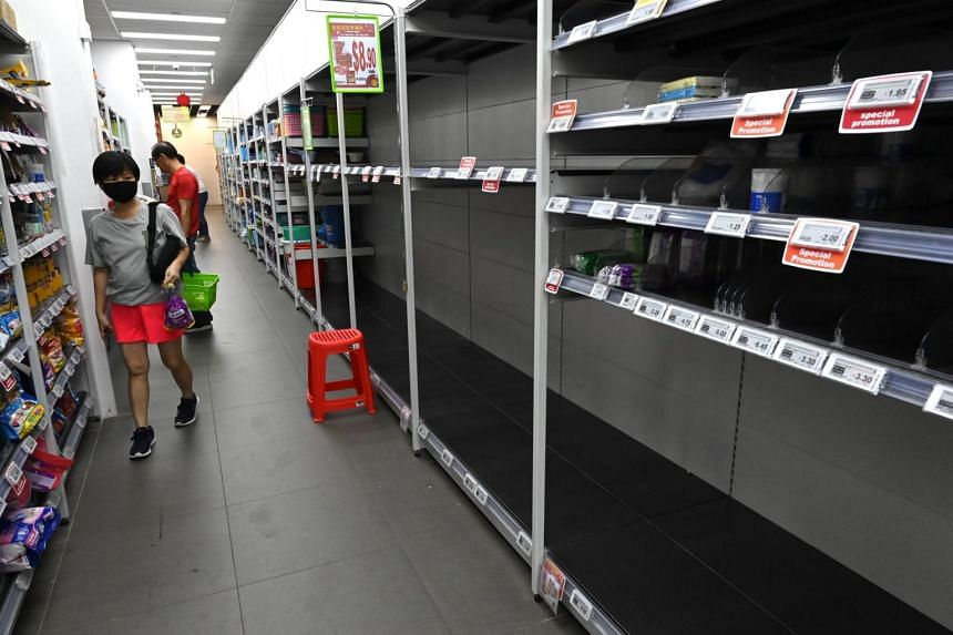 In a picture taken on Feb 8, 2020, a woman walks past empty shelves at a supermarket in Singapore after panic buying swept through the city when the Government raised the alert level for a coronavirus outbreak.