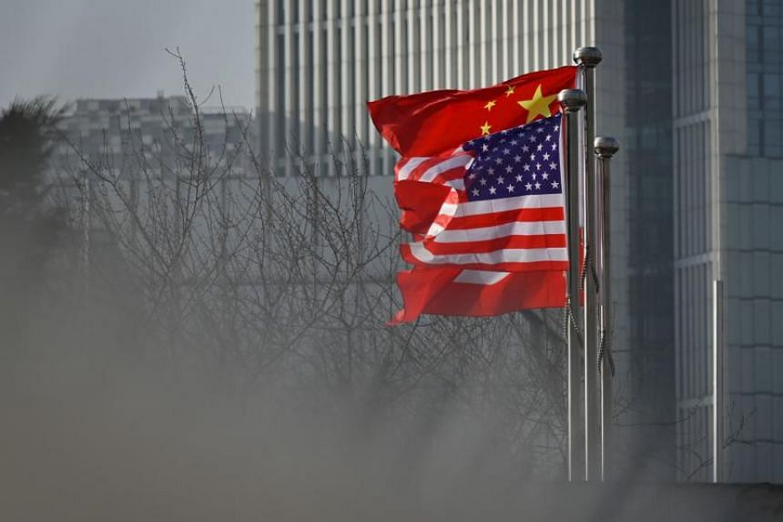 Chinese and US national flags flutter at the entrance of a company office building in Beijing on Jan 19, 2020.