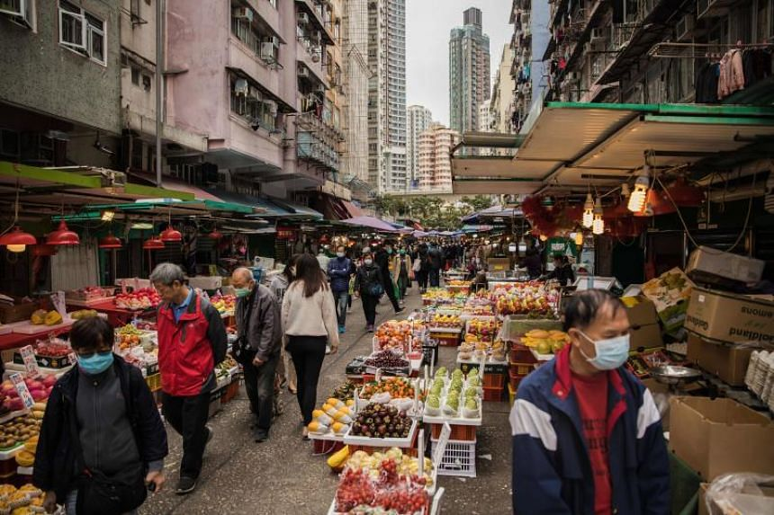 People wearing protective face masks shop at a fresh food market in Hong Kong on Feb 9, 2020.