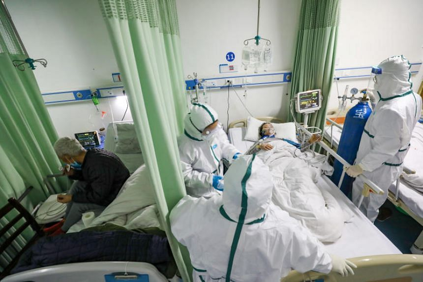 Medical workers in protective suits attend to a coronavirus patient at an isolated ward of a designated hospital in Wuhan, on Feb 6, 2020.