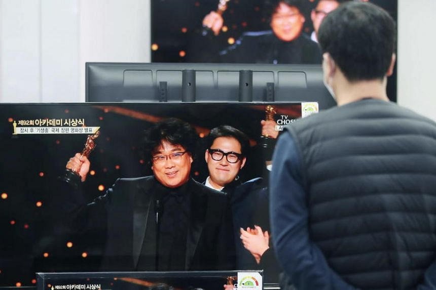 A man watches South Korean director Bong Joon-ho reacting after winning the best original screenplay award for his movie Parasite, on TV at a shop in Seoul, on Feb 10, 2020.