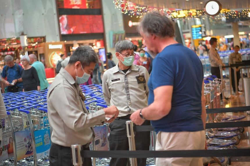 Travelers and airport staff wear protective masks at Changi Airport Terminal 3 on Feb 6, 2020.