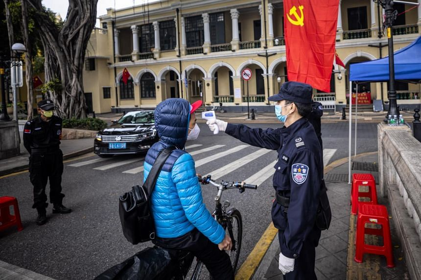 Security guards check the body temperature of a person passing by at a road blockade in Guangzhou, China, on Feb 10, 2020.
