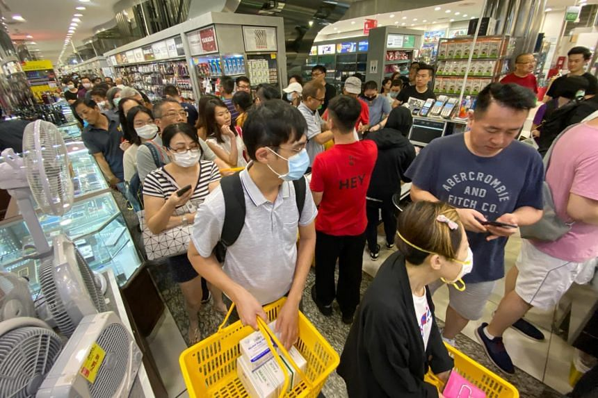 More than a hundred customers queue to buy masks at Mustafa store on Jan 28, 2020.