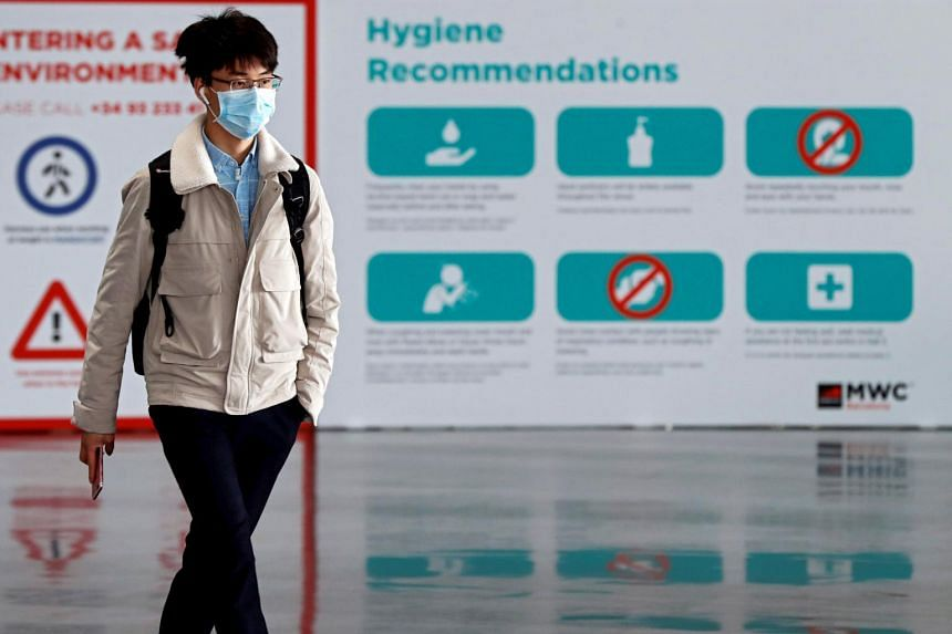 A worker wearing a mask leaves the Mobile World Congress' facilities in Barcelona, Spain, on Feb 7, 2020.