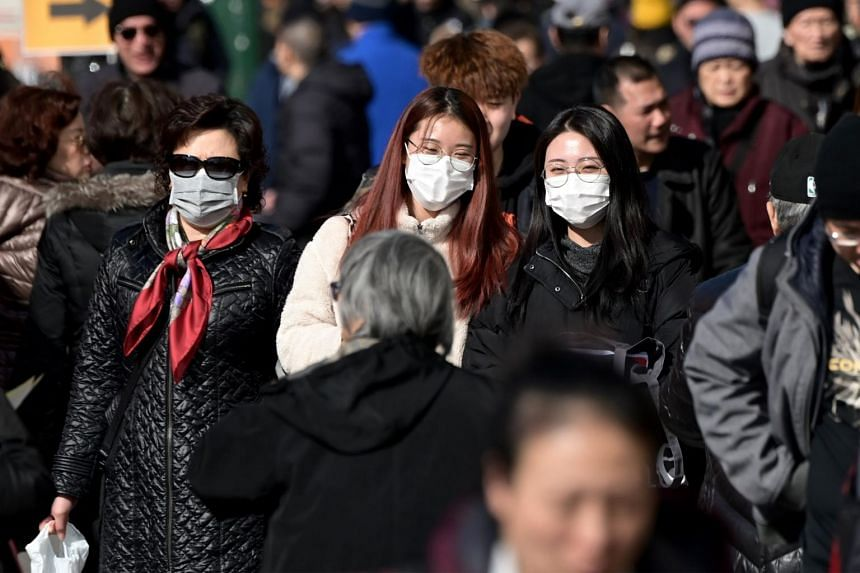 In a photo from Feb 3, 2020, people wear surgical masks in fear of the coronavirus in Flushing, a neighborhood in the New York City borough of Queens.