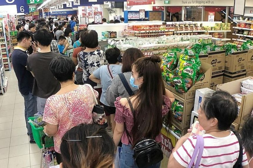 Shoppers queue to pay for essential items at the FairPrice supermarket at HDB Hub in Toa Payoh Feb 7, 2020.