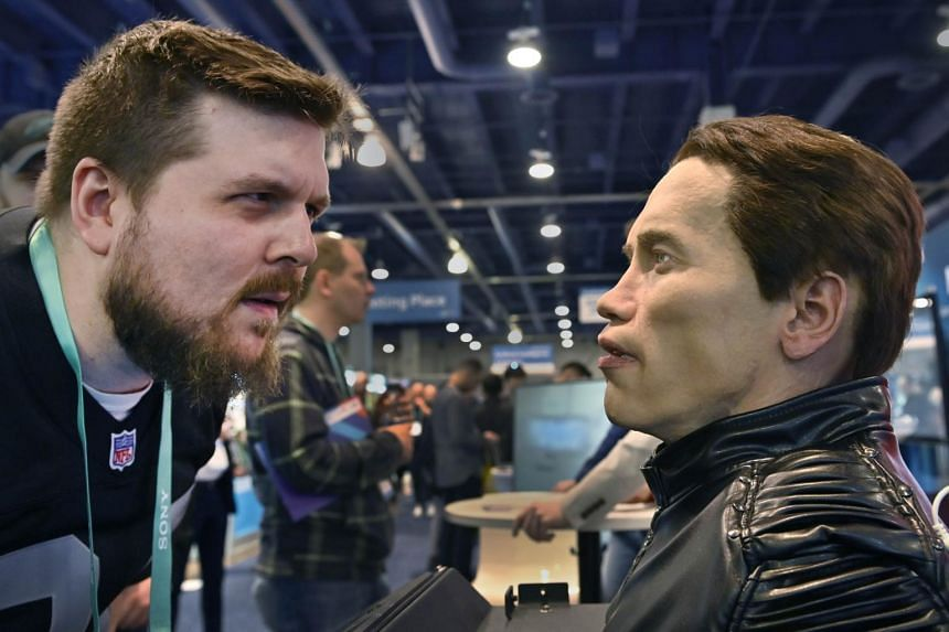 Attendee Brandon White (left) examines the Robo C, an autonomous humanoid robot at the Promobot booth during CES 2020 at the Las Vegas Convention Centre on Jan 8, 2020.