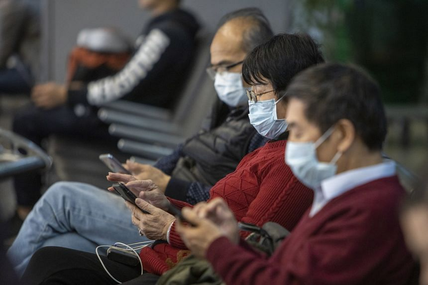 Travellers wear protective face masks in the arrival area at San Francisco International Airport on Feb 7, 2020.