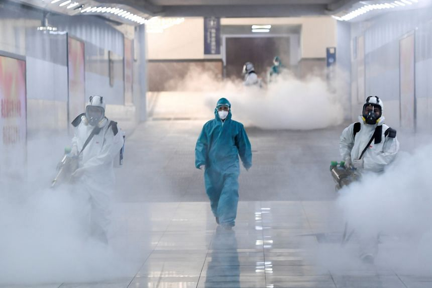 Volunteers in protective suits disinfect a railway station as the country is hit by an outbreak of the new coronavirus, in Changsha, Hunan province, China, on Feb 4, 2020.
