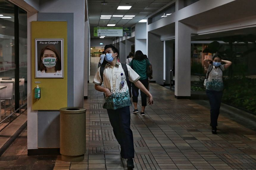 Hospital staff with face masks walk past a poster in Singapore General Hospital on Jan 23, 2020.