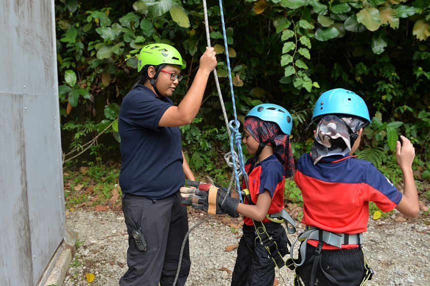 In a photo dated April 5, 2016, an outdoor adventure educator is seen helping Farrer Park Primary School pupils during a three-day camp at the Dairy Farm Outdoor Adventure Learning Centre.