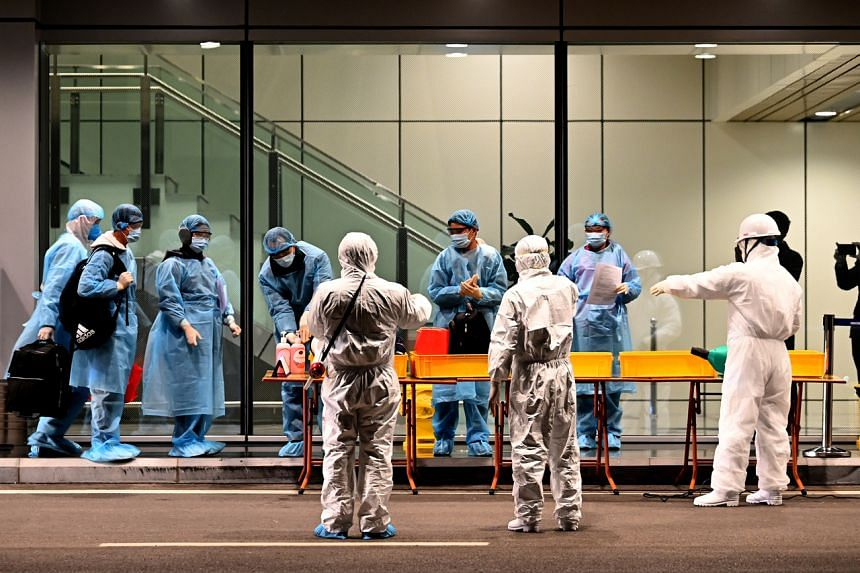 Vietnamese people repatriated from Wuhan wearing protective suits arrive at the Van Don airport, in Vietnam on Feb 10, 2020.