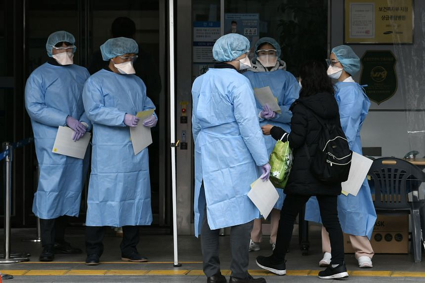 Hospital officials wearing protective gear guide visitors to help prevent the spread of the coronavirus at the entrance of a hospital in Seoul on Feb 4, 2020.