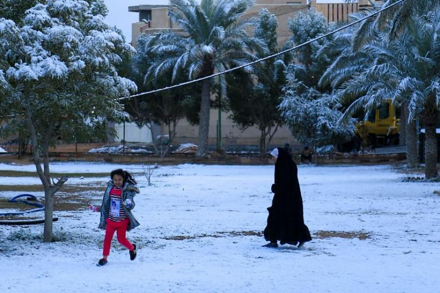 A girl plays in the snow in Karbala, Iraq, on Feb 11, 2020.