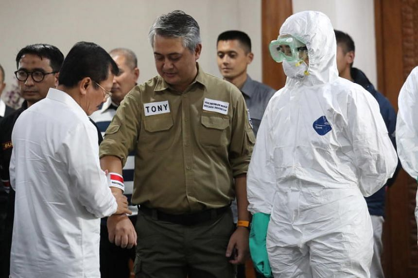 A photo taken on Feb 1, 2020, shows Indonesian Health Minister Terawan Agus Putranto (left) with Indonesian air crew involved in a humanitarian operation to pick up Indonesians from Wuhan, China, at Soekarno-Hatta International Airport in Banten, Ind