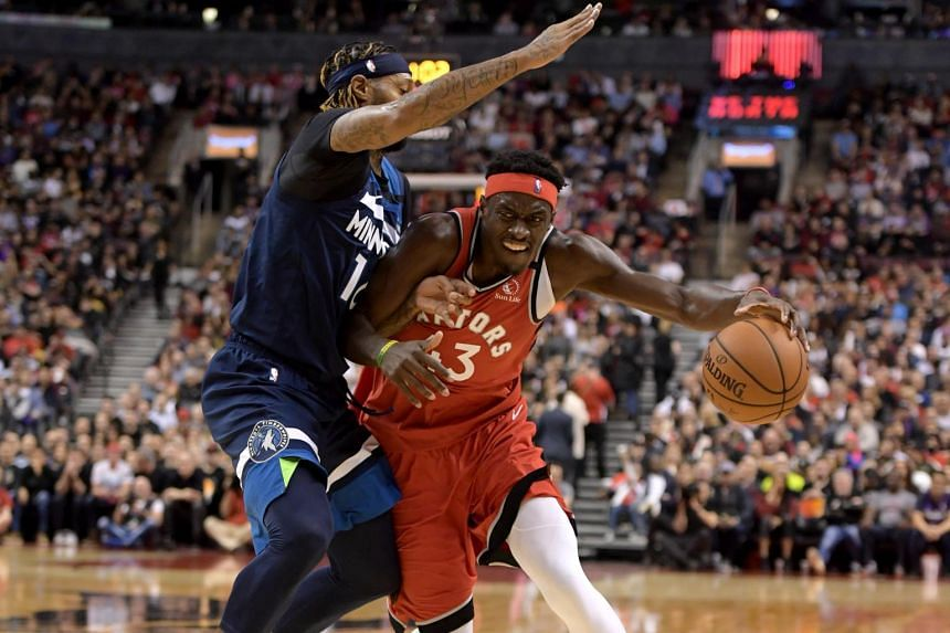 Pascal Siakam of the Toronto Raptors (in red) dribbles the ball past Minnesota Timberwolves forward James Johnson during an NBA basketball game in Scotiabank Arena, Toronto, on Feb 10, 2020.