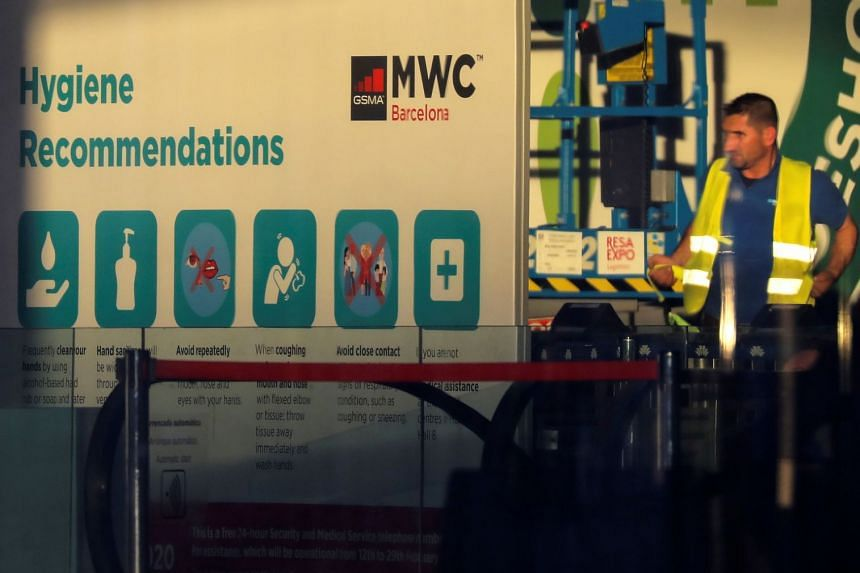 An employee is pictured next to a banner with information on MWC20 in Barcelona, Spain.