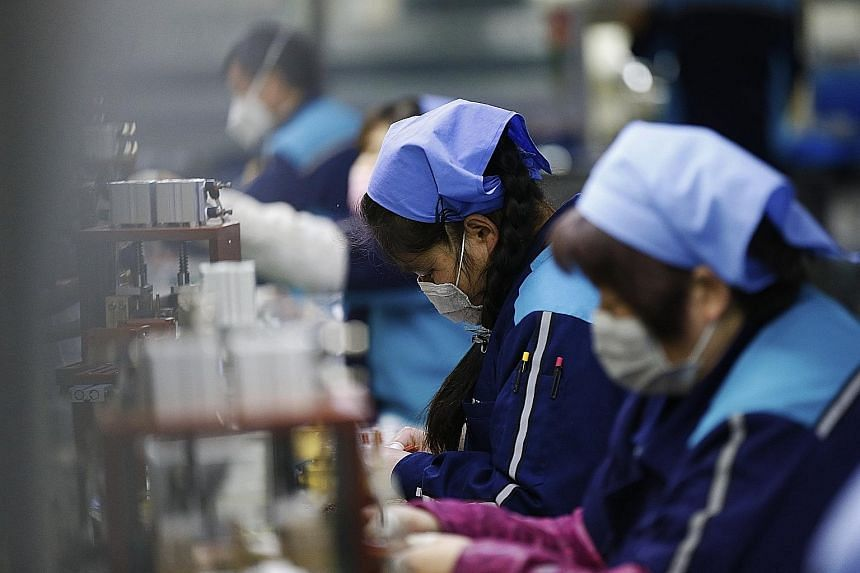 Workers at an electronic components factory in Sihong county, Jiangsu province, on Monday. The coronavirus outbreak in China could lead to extended factory closures that will slow manufacturing and weigh on global supply chains.