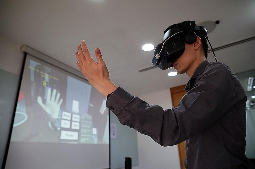 Mr Aaron Ng, a senior executive at NEA's Vector Control Section, demonstrating the use of VR gear in a dengue home inspection scenario. He said the virtual reality training module would help officers experience more scenarios and hone their reaction