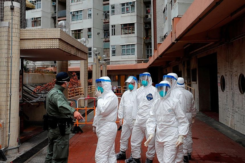 Police in protective gear waiting to evacuate residents from a public housing building in Hong Kong's Tsing Yi district yesterday. The building has two confirmed coronavirus cases.