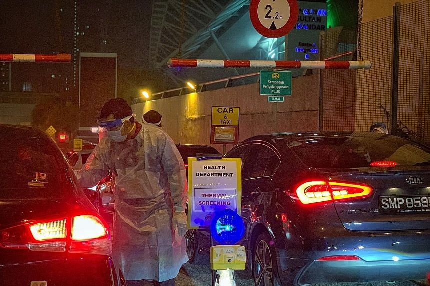 Thermal scanning being conducted on travellers at the Johor Baru Customs, Immigration and Quarantine complex on Monday. ST PHOTO: ARIFFIN JAMAR