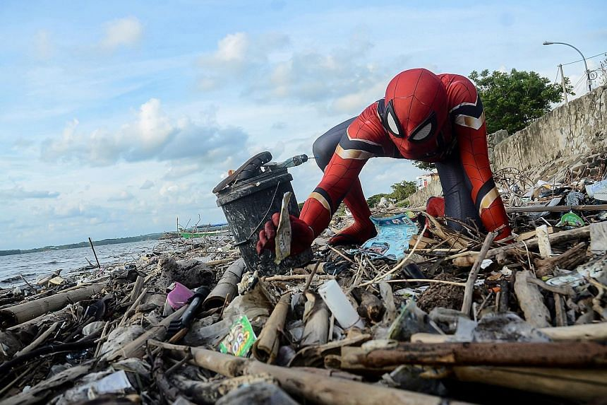 """""""Spider-Man"""" Rudi Hartono channelling a famous quote in the superhero's comics - with great power comes great responsibility - by collecting rubbish at a beach in Pare-Pare, South Sulawesi. Before he hit on the idea of wearing the costume, he did not"""