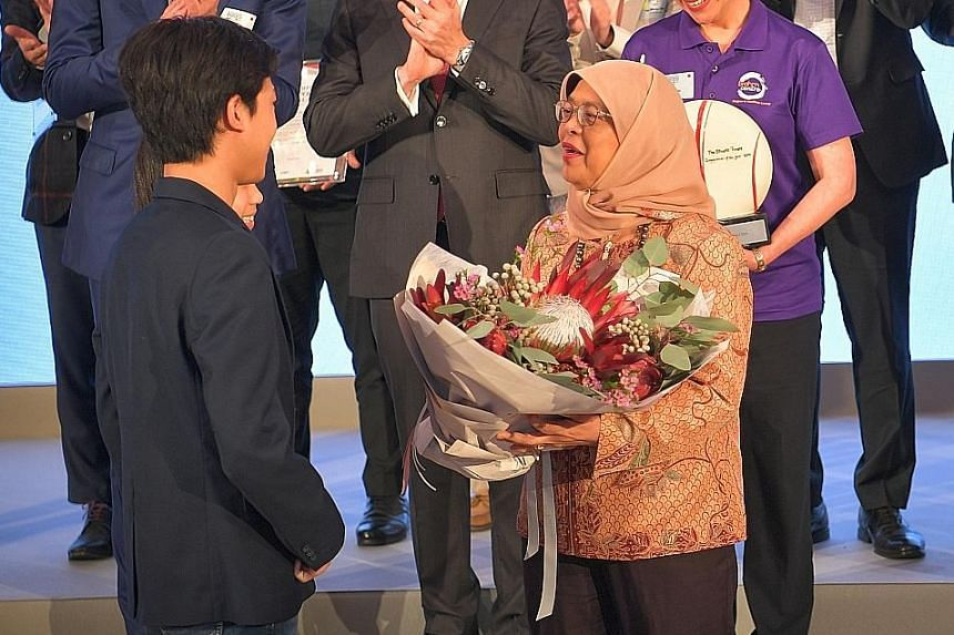 President Halimah Yacob receiving a bouquet from two young finalists of the award - siblings and students Seng Ian Hao and Seng Ing Le - during yesterday's ceremony.