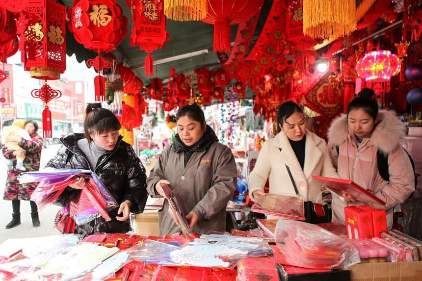 People buying Chinese New Year decorations on Dec 24, 2019, at a market in Chongqing, China, where the authorities have banned large gatherings as they try to rein in the virus epidemic.