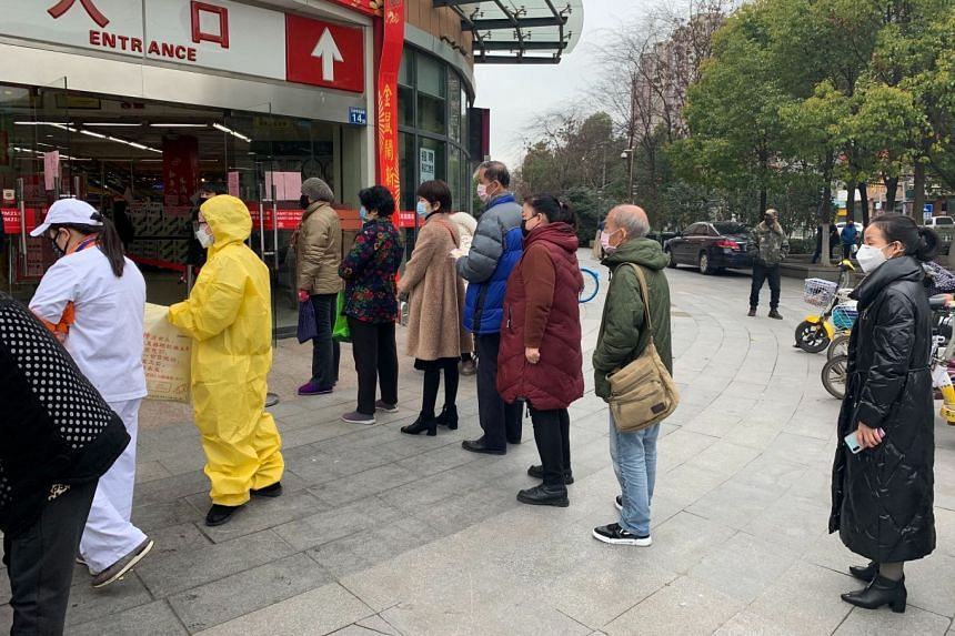 Residents wait to enter a supermarket in Wuhan, China on Feb 11, 2020, that limited the number of shoppers allowed inside the store in response to the coronavirus epidemic.