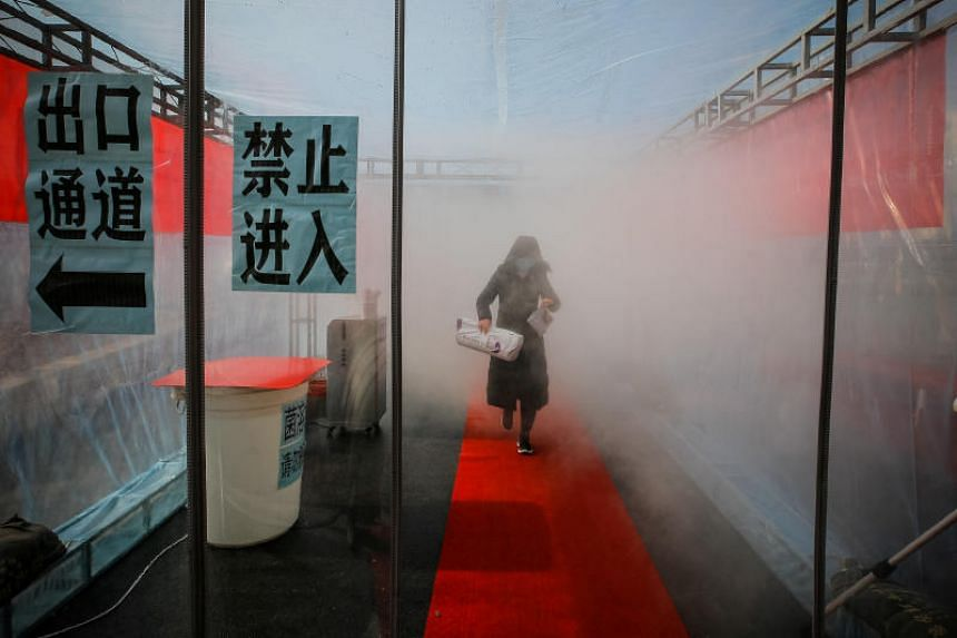 A device that sprays disinfectant at an entrance to a residential compound in Tianjin, China. Of 102 confirmed cases in Tianjin, at least 33 patients worked or shopped at a department store in the Baodi district.