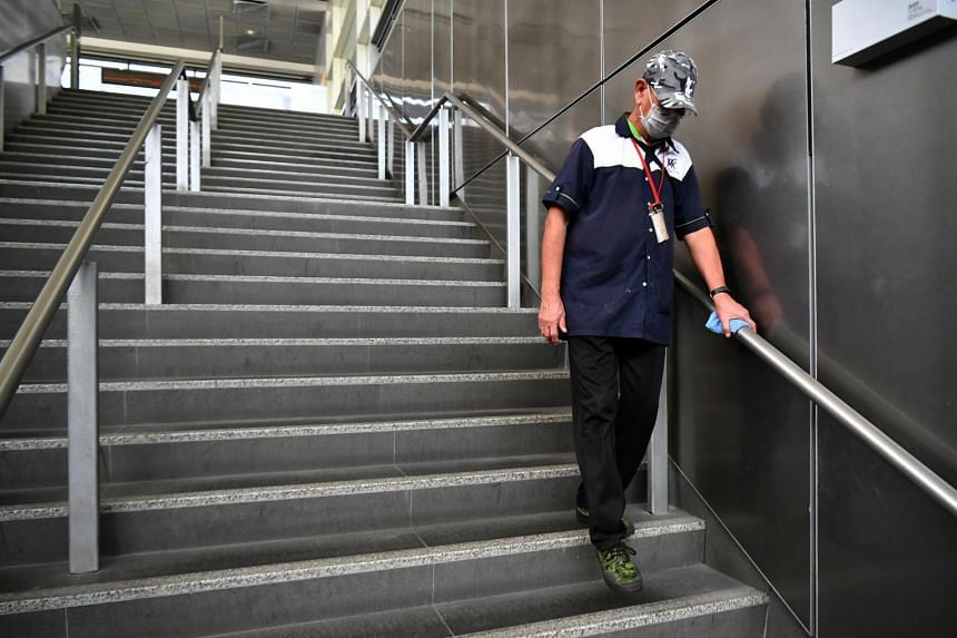 A cleaner wiping the handrail at Paya Lebar MRT station.