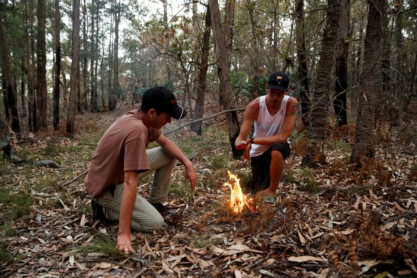 Indigenous Australians Oliver Costello of Firesticks Alliance (left) and Jacob Morris demonstrate cultural burning in a forest in Illaroo, New South Wales, Australia, on Jan 22, 2020.