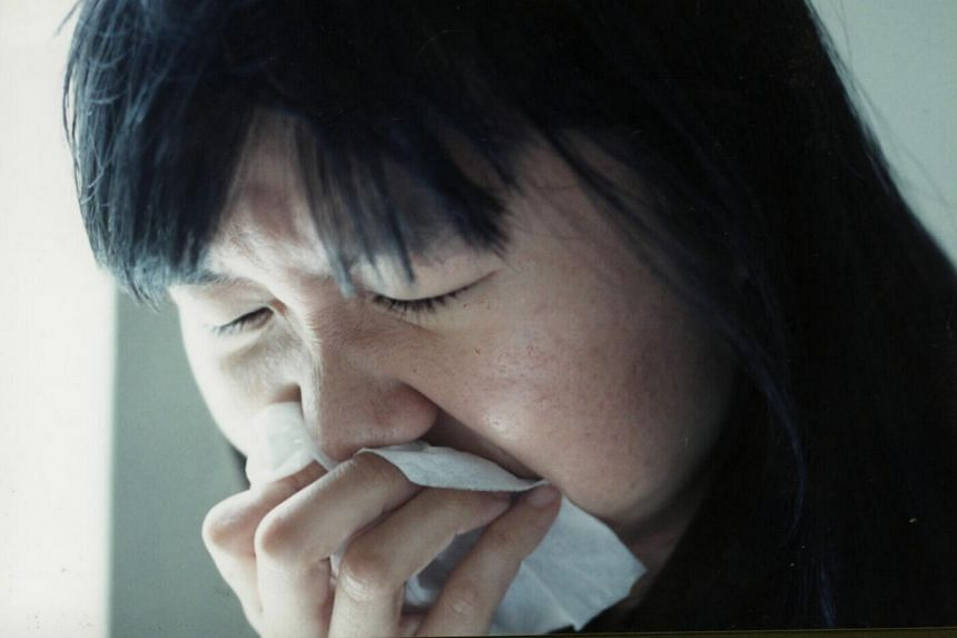 A woman covering her mouth and nose.