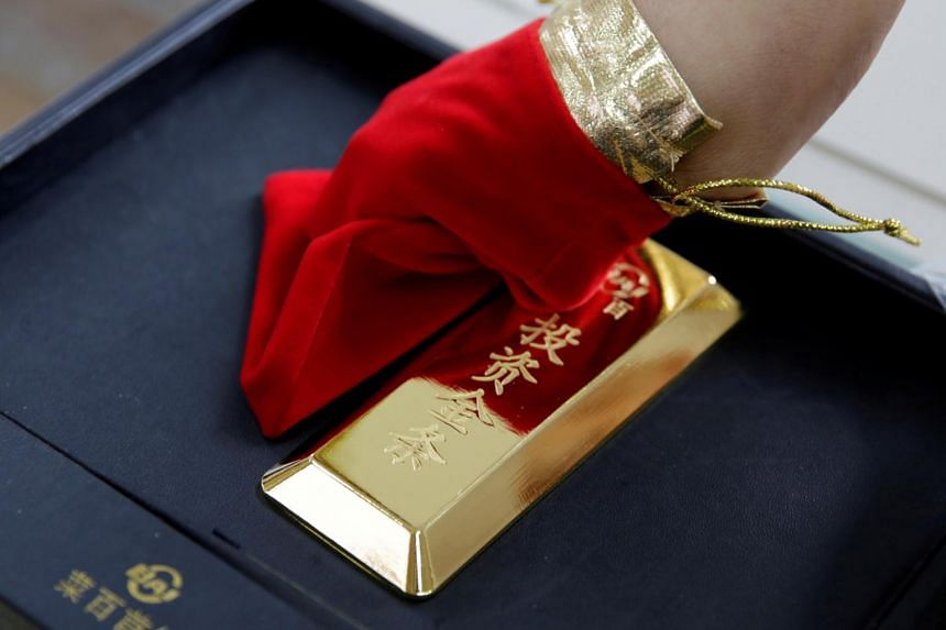 A sales assistant displays a 1,000 gram gold bar as an investment for a customer at Caibai Jewelry store, in Beijing, China, on Aug 6, 2019.