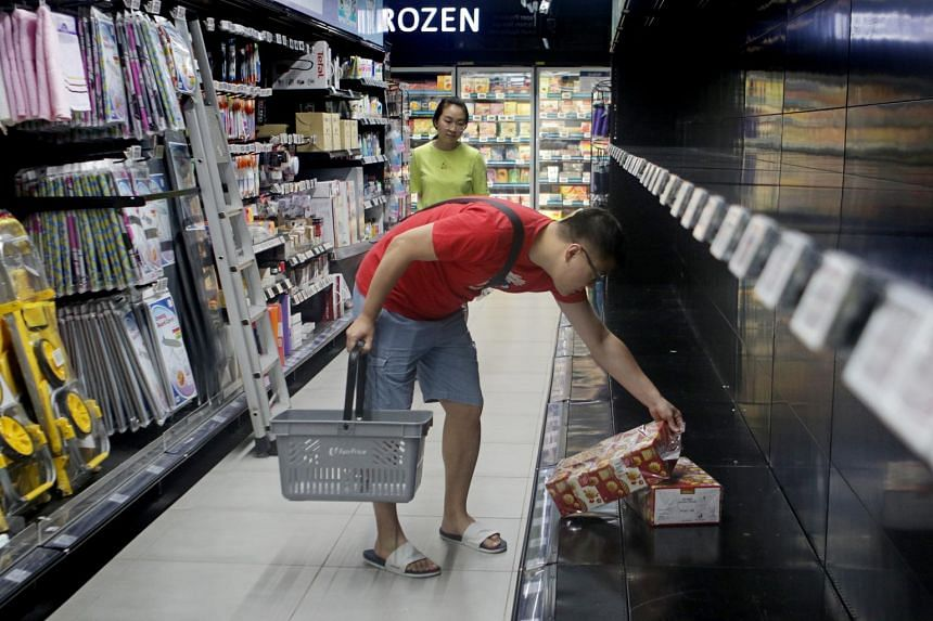 A man buying the last remaining box of tissue paper at a NTUC Fairprice Finest outlet at Paya Lebar, on Feb 8, 2020.