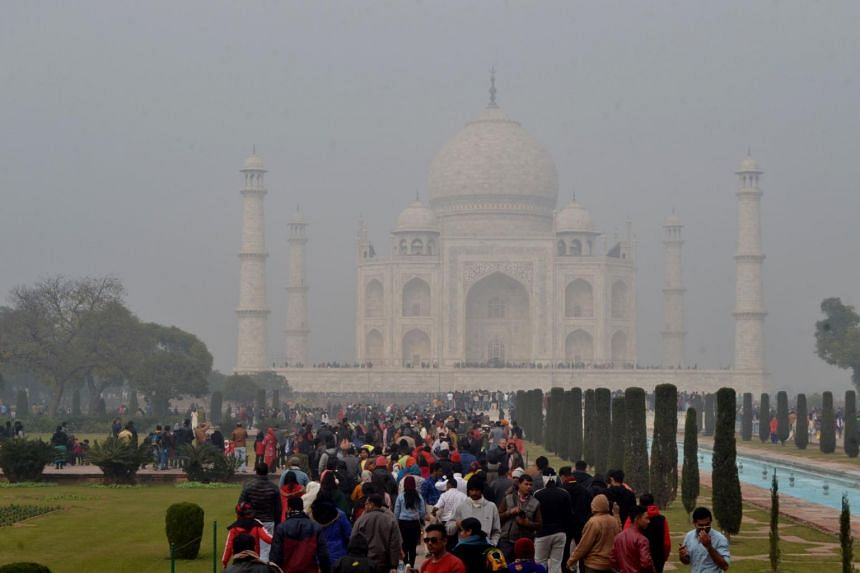 Tourists visit The Taj Mahal under heavy smog conditions in Agra, on Dec 28, 2019.