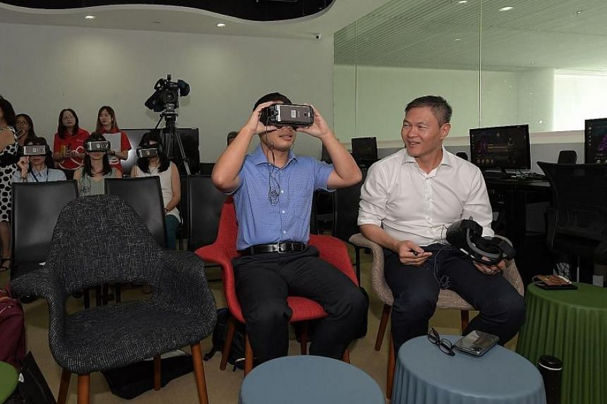 Minister for Social and Family Development Desmond Lee (centre) and Touch Community Services chief executive James Tan trying on virtual reality headsets at Touch Community Services at Leisure Park Kallang yesterday. Mr Lee tried out the Virtual Real