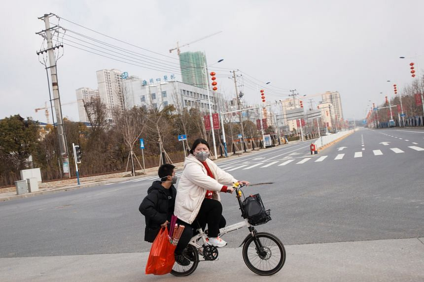 People wear face masks as they cycle in an empty street in the Yunxi county, Hunan province, near the border to Hubei province, on Jan 28, 2020.