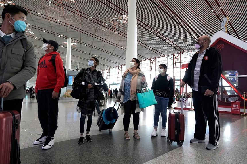 Foreign travellers checking their flight's departure information at Beijing International Airport on Feb 1, 2020. The Civil Aviation Administration of China will continue to lobby authorities to subsidise airlines hurt by travel curbs due to the coro