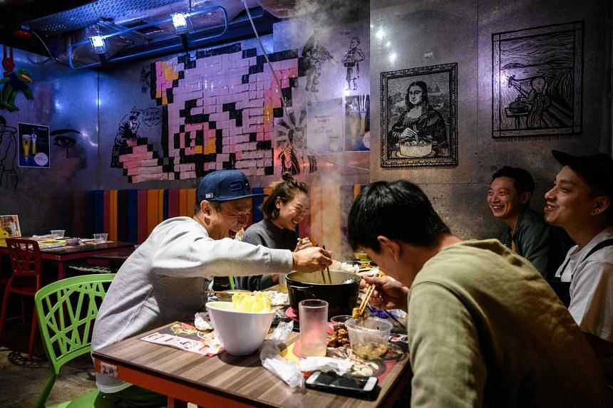A group of friends eat together at 66 Hotpot, a family-run restaurant in the bustling district of Mongkok in Hong Kong, on Feb 11, 2020.