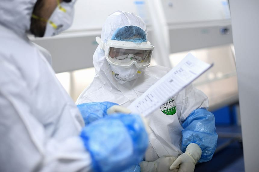 A photo taken on Feb 6, 2020, shows laboratory technicians working on samples from people to be tested for the coronavirus at a laboratory in Wuhan.