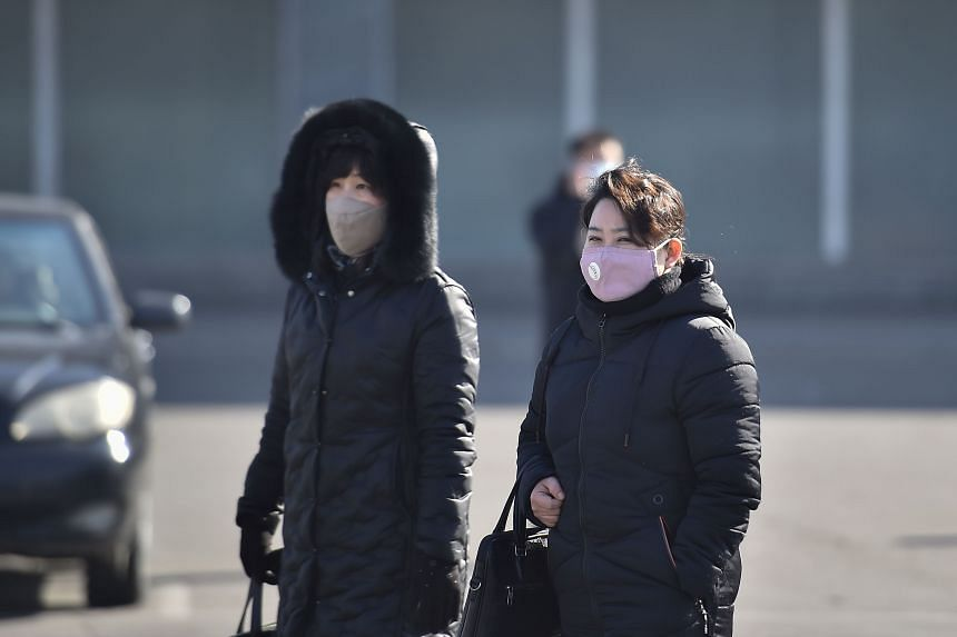 People wearing face masks walk in Pyongyang, on Feb 6, 2020.