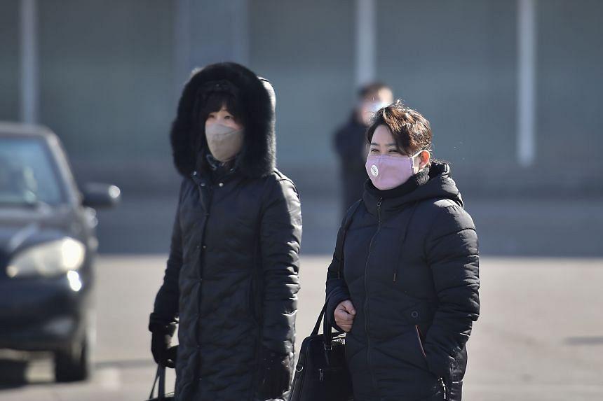 People wearing face masks walk in Pyongyang, on Feb 6, 2020.