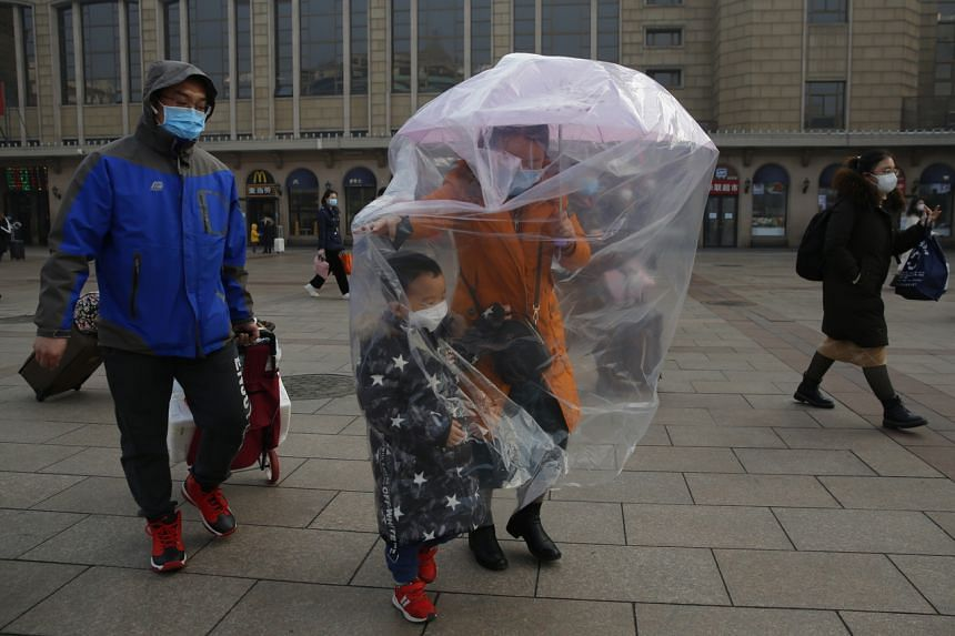 A passenger wears a protective mask and covers herself and her child with a plastic bag at the Beijing railway station on Feb 11, 2020.