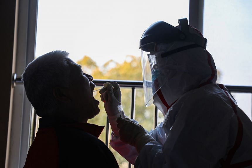 A photo taken on Feb 4, 2020, shows a medical staff member taking samples from a person to be tested for the coronavirus at a quarantine zone in Wuhan.