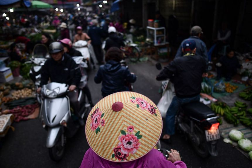 A Vietnamese woman (centre) wearing a traditional conical hat, makes her way through a busy morning market in Hanoi, on Jan 14, 2020.